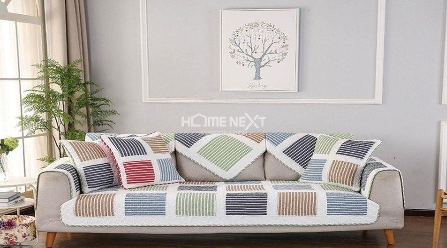Chiếc ghế sofa với tấm thảm có họa tiết rực rỡ mang lại nguồn năng lượng tích cực cho căn hộ